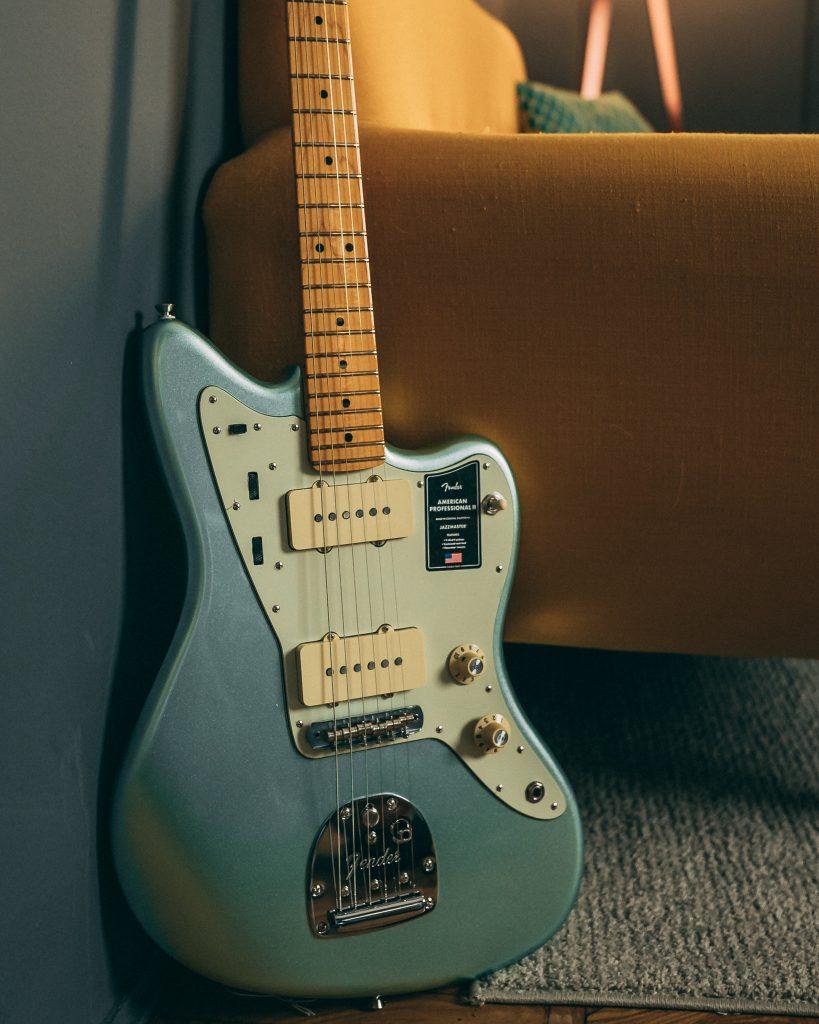 Chitarra elettrica Fender American Professional II Jazzmaster in finitura Surf Green con divano giallo.