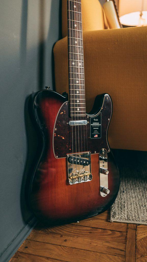 Chitarra elettrica Fender American Professional II Telecaster in finitura Sunburst con divano giallo.